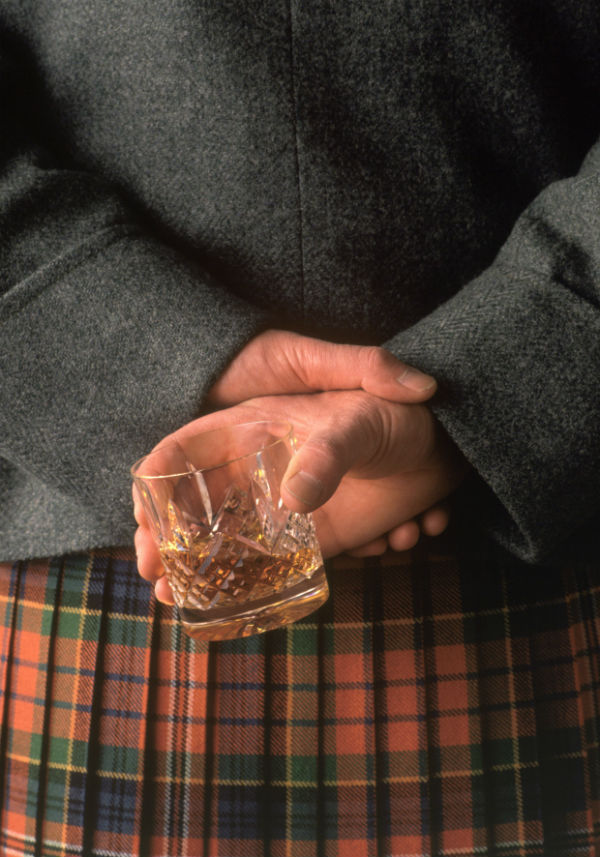 Scottish kilt man holding a whisky dram