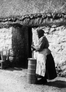 Tiree typical thatch hoose with woman outside, not even height of the door